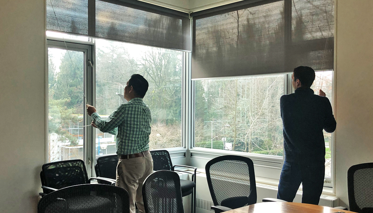 Staff from school of journalism take down window shades